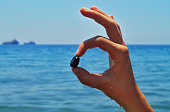 Close-up of a wet right hand in OK gesture with a small black stone in front of the blue sea and clear sky on the summer sunny day