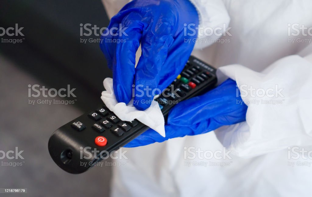 Hand in protective glove with napkin cleaning remote control. Covid-19 disinfection concept. Hand in protective glove with napkin cleaning remote control. Covid-19 disinfection concept. Adult Stock Photo