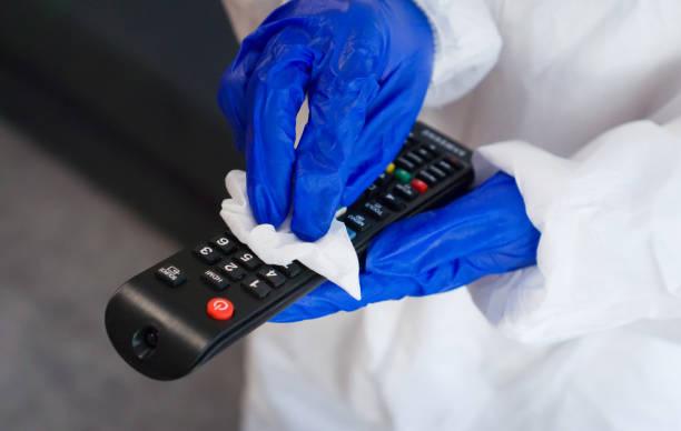 hand in protective glove with napkin cleaning remote control. covid-19 disinfection concept. - capelli ossigenati foto e immagini stock