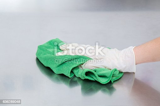 istock Hand in protective glove with rag cleaning kitchen equipment. 636289048