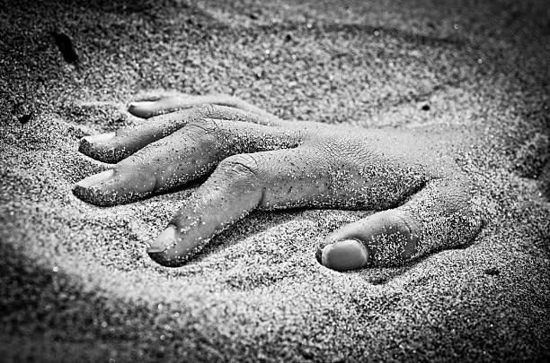 hand in rigor mortis on the beach stock photo