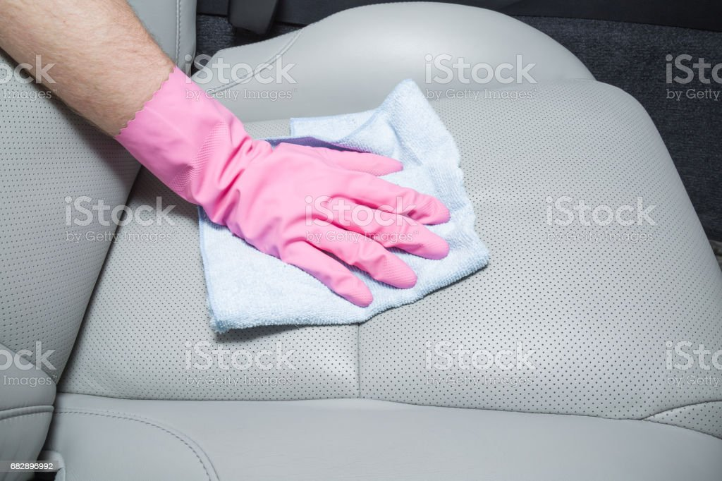 Hand in rubber protective glove with cloth cleaning a car interior's leather seats. Early spring professionally chemical cleaning or regular clean up. Lizenzfreies stock-foto