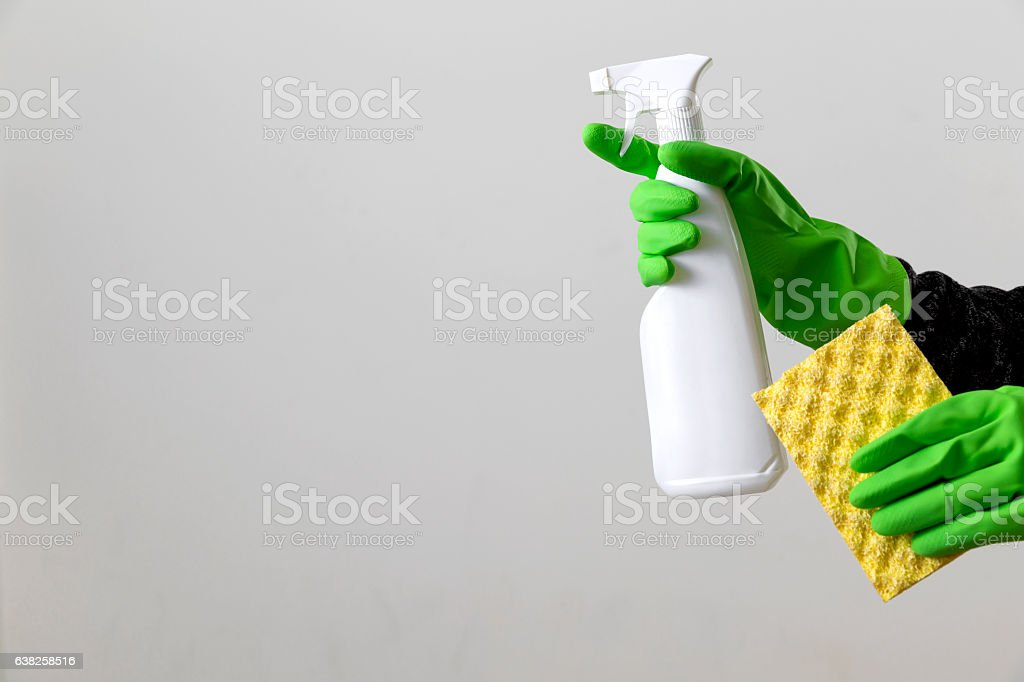 Hand in rubber protective gloves holding bottle of detergent stock photo