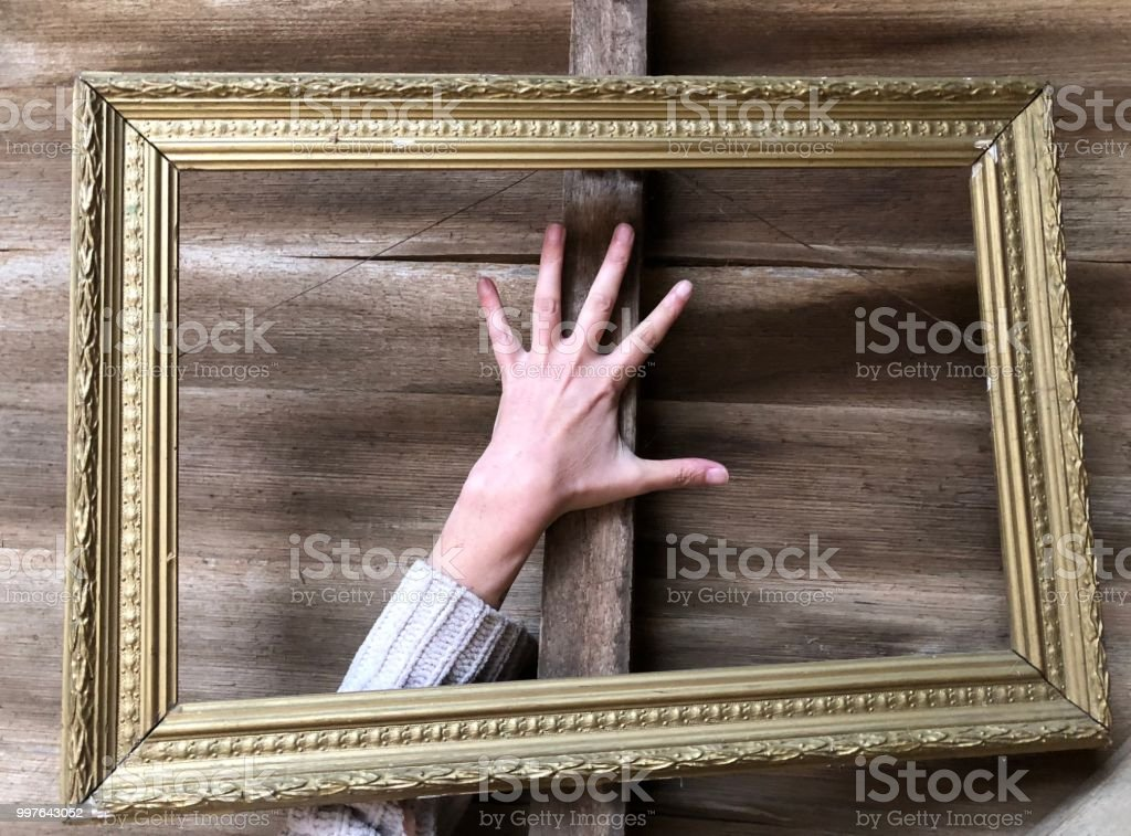 Close up of an empty picture frame with a human hand in it