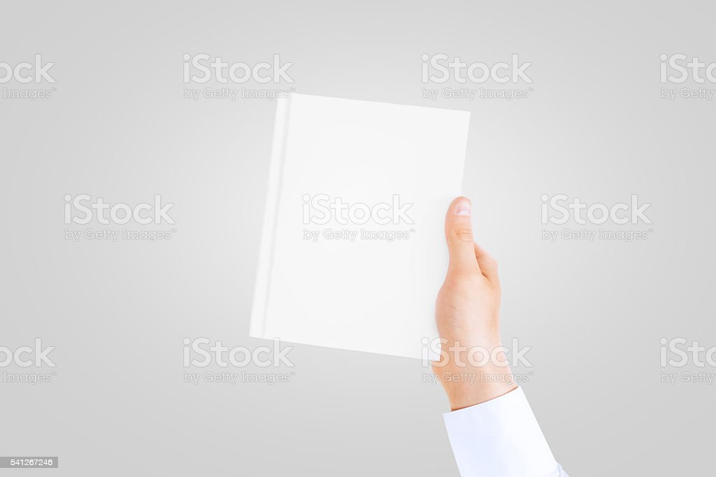 Hand in white shirt sleeve holding closed blank book.