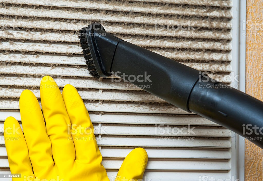 Hand in yellow glove and vacuum cleaner pipe stock photo