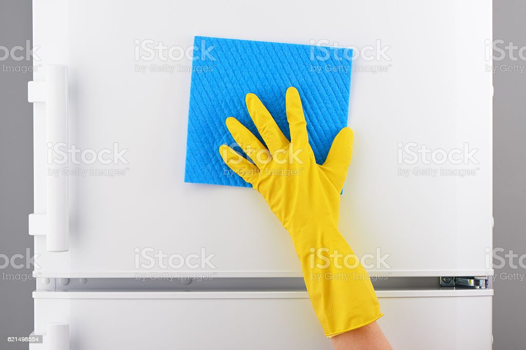 Hand in yellow glove cleaning white refrigerator with blue rag photo libre de droits