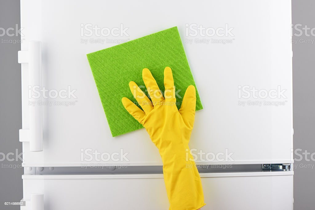 Hand in yellow glove cleaning white refrigerator with green rag photo libre de droits