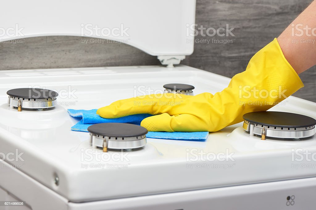 Hand in yellow glove cleaning white stove with blue rag foto stock royalty-free