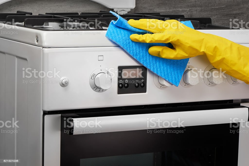 Hand in yellow glove cleaning white stove with blue rag Lizenzfreies stock-foto