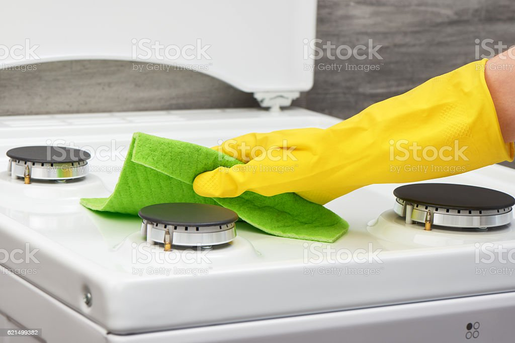 Hand in yellow glove cleaning white stove with green rag Lizenzfreies stock-foto