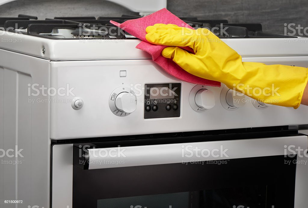 Hand in yellow glove cleaning white stove with pink rag photo libre de droits