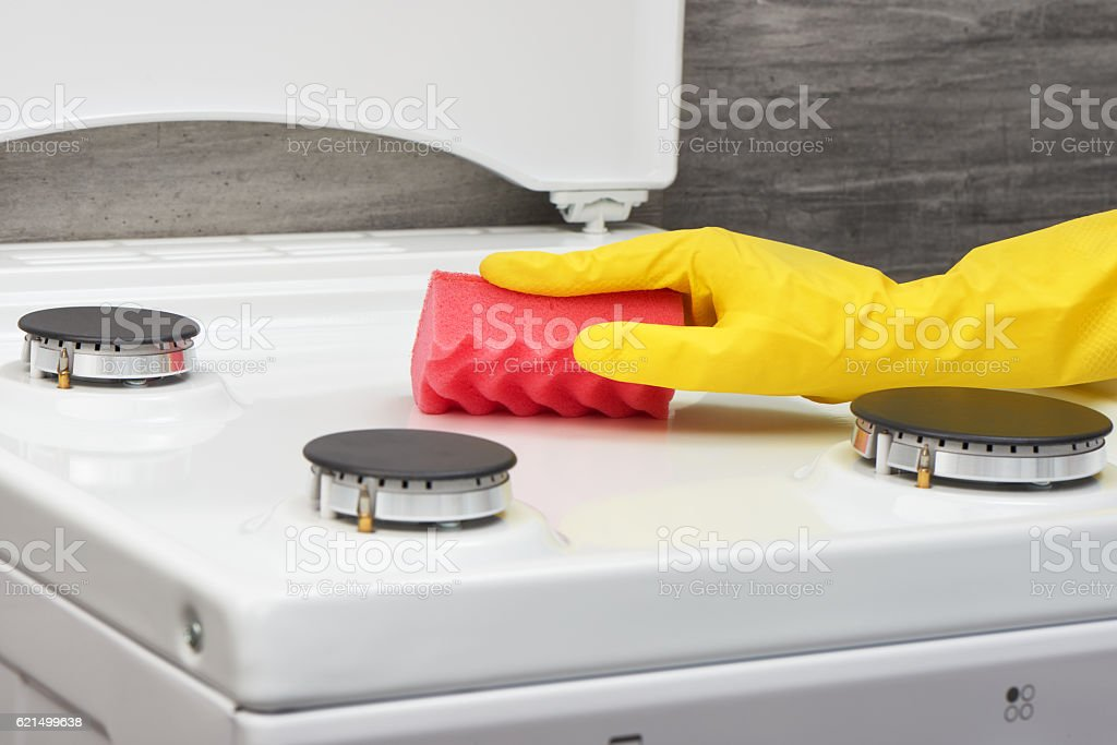 Hand in yellow glove cleaning white stove with pink sponge photo libre de droits