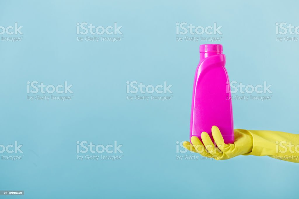 Hand In Yellow Glove Holds A Bottle Of Bleach On White Background Cleaning Royalty