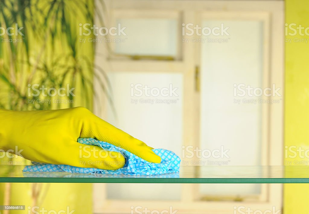 Hand in yellow gloves doing spring cleaning royalty-free stock photo