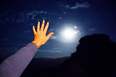 Hand infront of defocused full moon at night