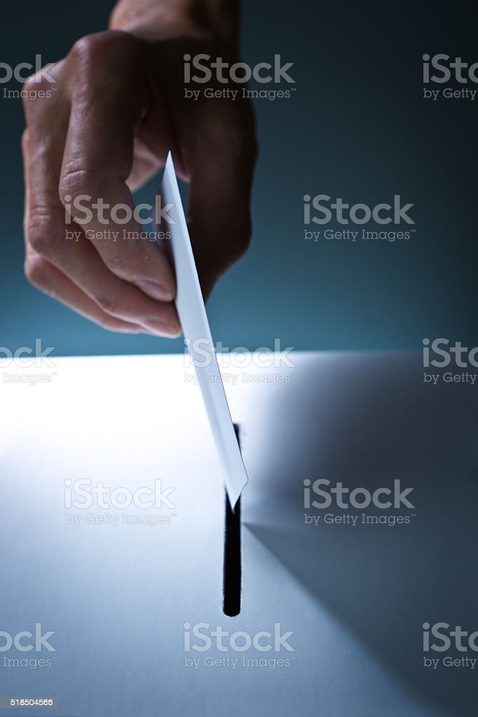 Hand Inserting a Voting Card into a Slot of a Ballot Box stock photo