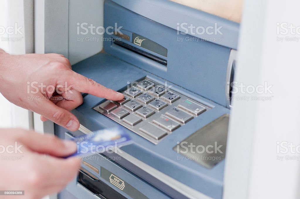Hand inserting ATM card into bank machine to withdraw money stock photo