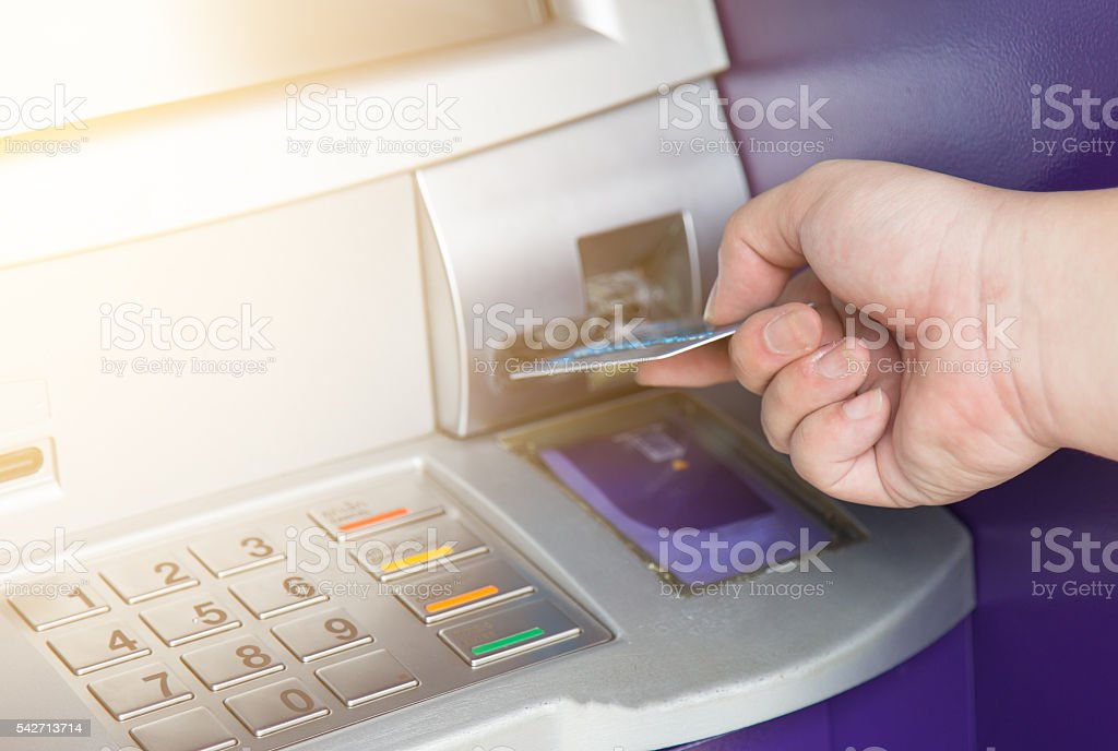 Hand inserting ATM credit card into bank machine stock photo