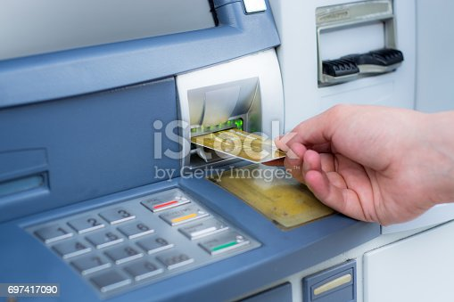 istock Hand inserting ATM credit card 697417090