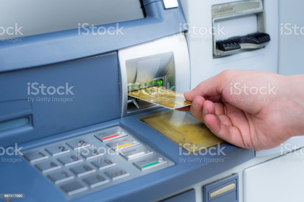 Hand inserting ATM credit card stock photo