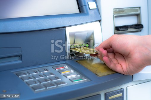 istock Hand inserting ATM credit card 697417092