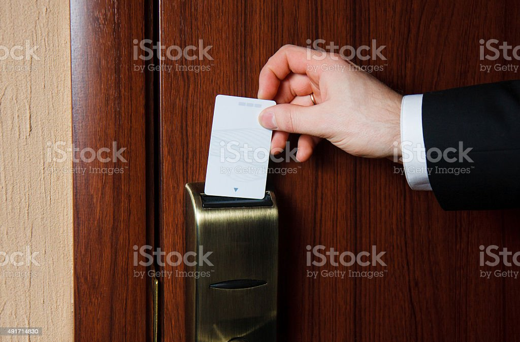 Hand inserting card into electronic lock in hotel stock photo