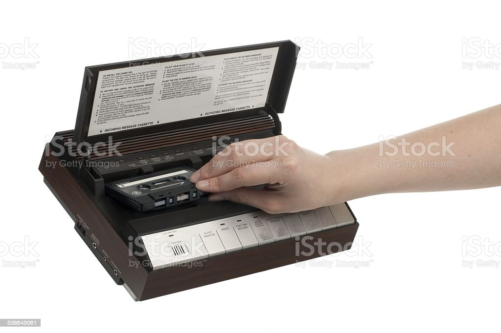 hand inserting cassette in an answering machine stock photo