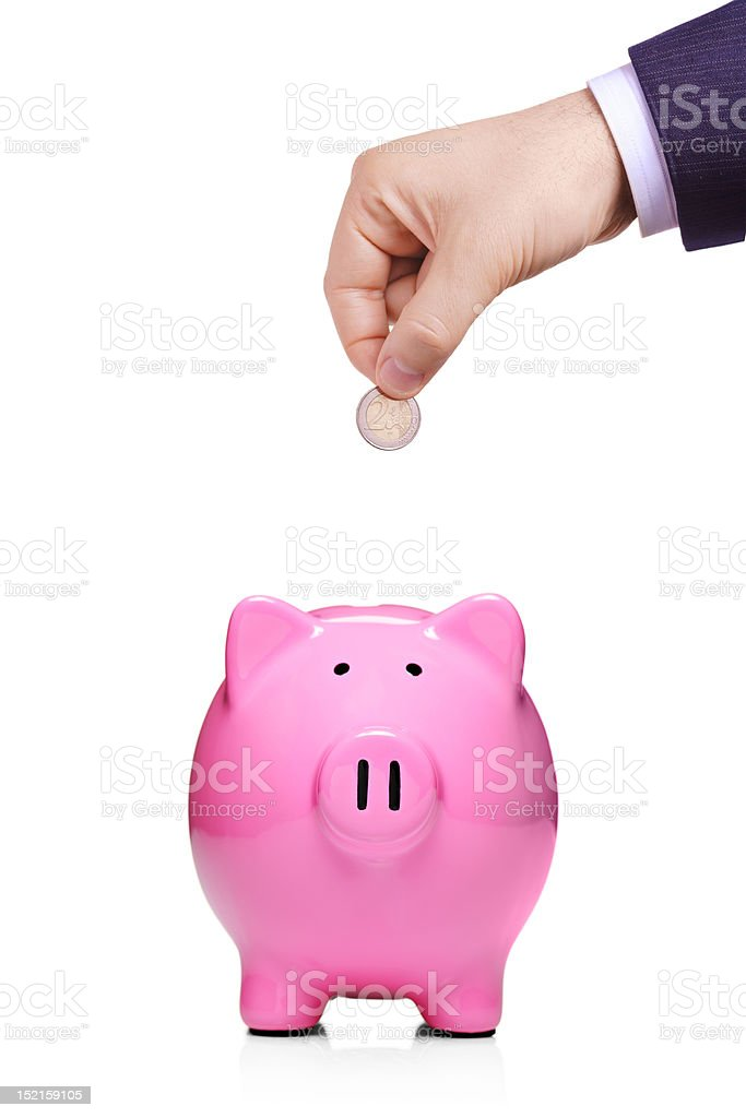 Hand inserting coin into piggybank royalty-free stock photo
