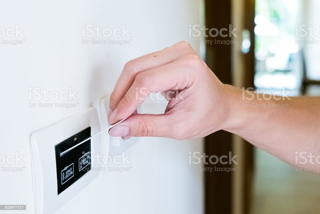 hand inserting hotel keycard stock photo