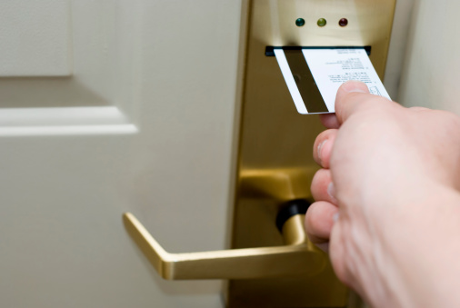 Male hand inserting a magnetic strip keycard into a electronic hotel door lock to unlock the door.