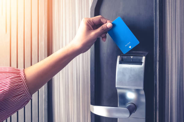 Hand inserting key card to unlock a door security authentication in the hotel or apartment safeguard Hand inserting key card to unlock a door security authentication in the hotel or apartment safeguard. cardkey stock pictures, royalty-free photos & images