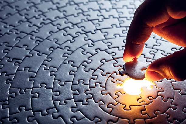 hand inserting missing puzzle piece - puzzles stock photos and pictures