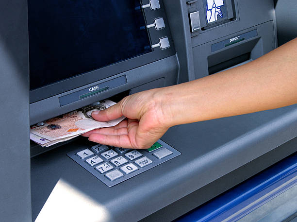 Hand inserting money into an ATM machine stock photo