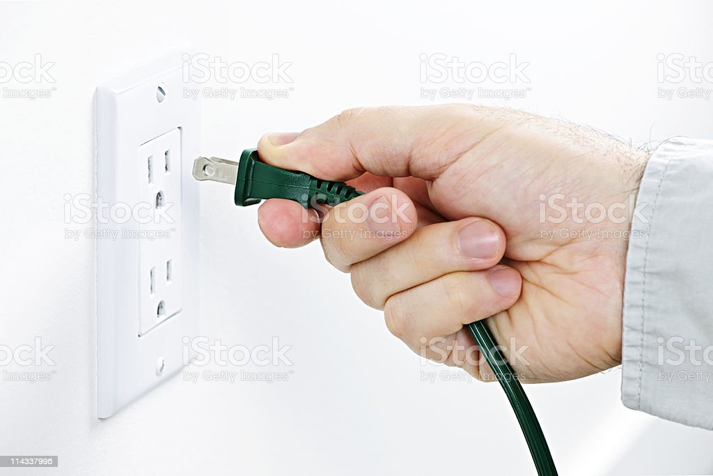 Hand inserting plug into outlet royalty-free stock photo