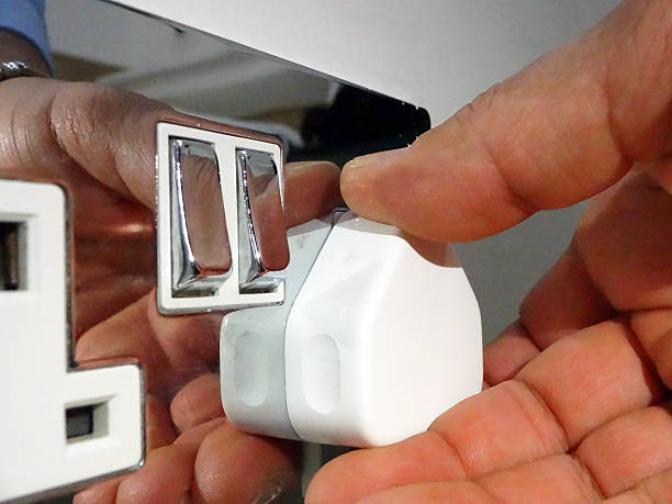 Hand inserting uk plug into uk socket stock photo