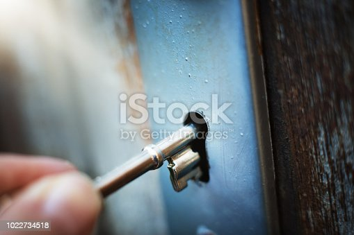 A hand inserts a key in a mortice type lock in a door.