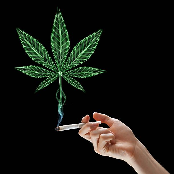 A hand is holding a cigarette depicting smoking marijuana stock photo