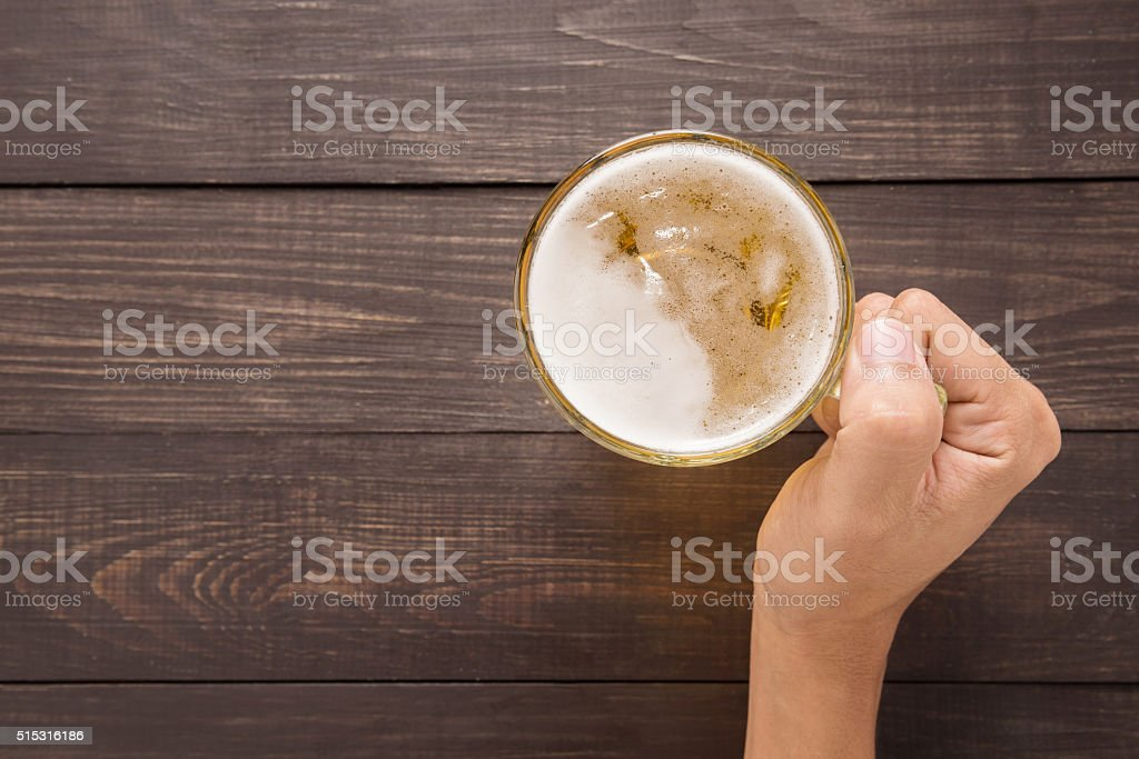 Hand is holding a glass of beer in the pub stock photo
