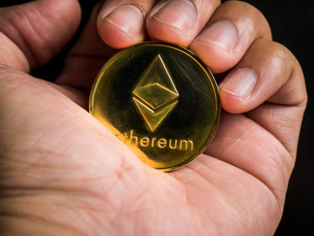 Hand is holding gold ethereum coin. stock photo