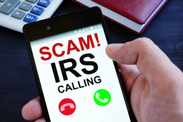 Hand is holding phone with irs scam calls. stock photo