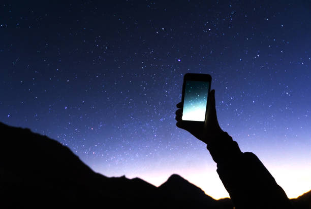 a hand is holding smartphone with starry sky photo: a man is taking a photo starry sky at night. milky way and galaxy on dark sky. wifi mobile internet concept - astronomy stock pictures, royalty-free photos & images