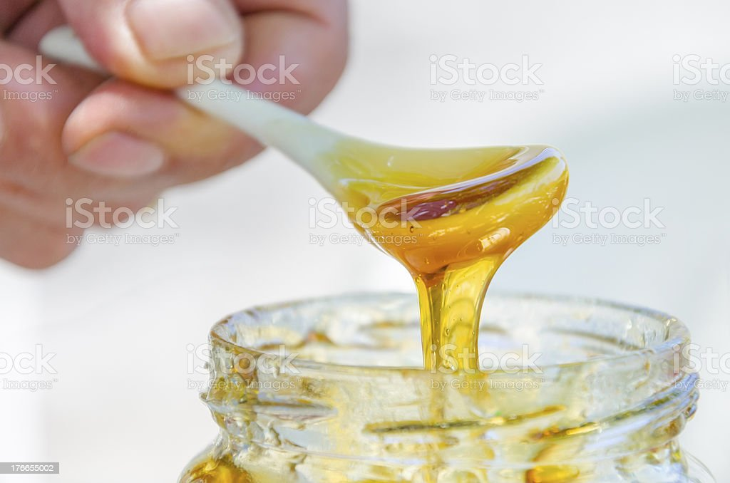 hand is pouring honey from porcelan spoon drizzler royalty-free stock photo