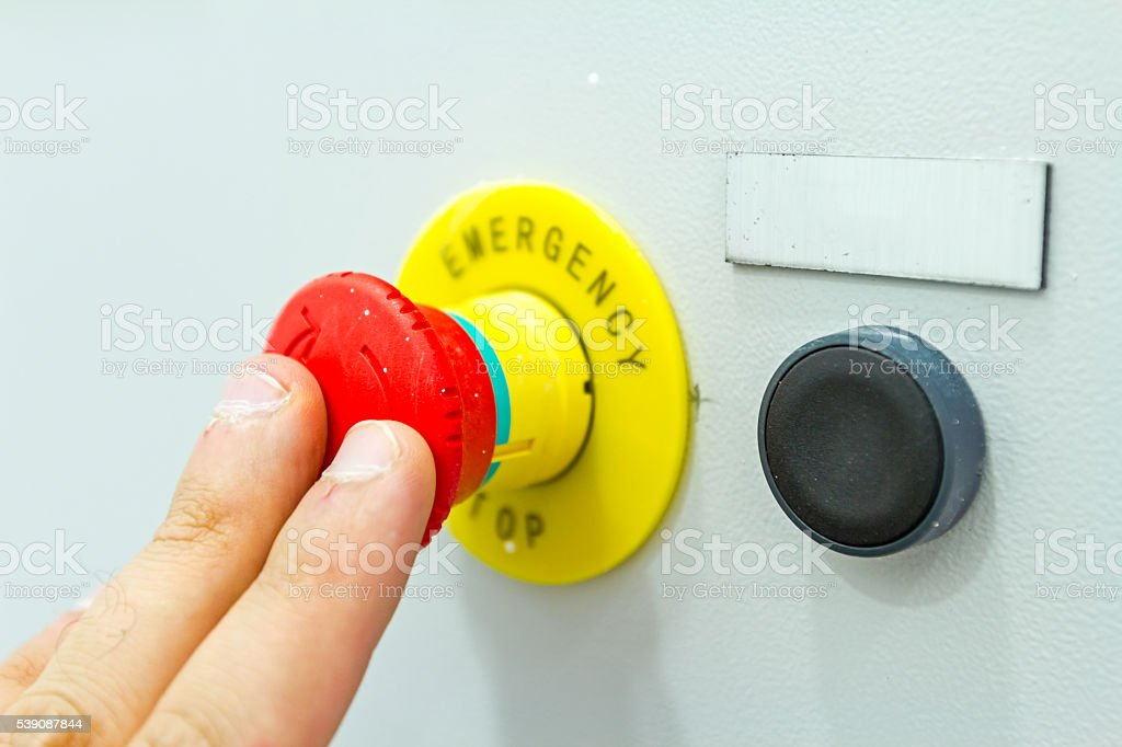 Hand is pushing emergency red stop button stock photo