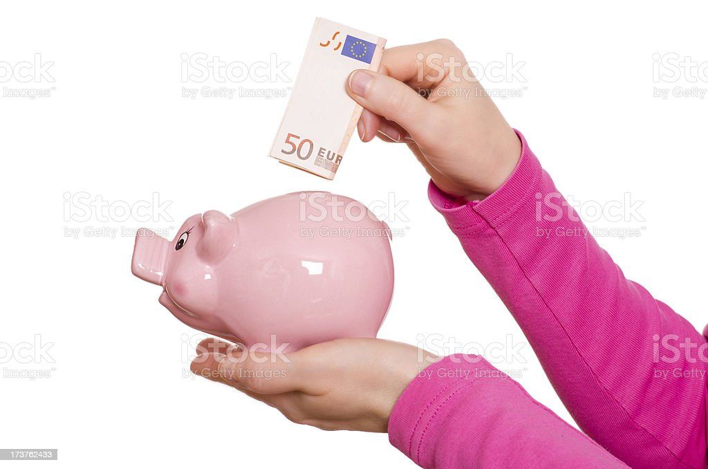 Hand is putting euro note into a piggy bank royalty-free stock photo