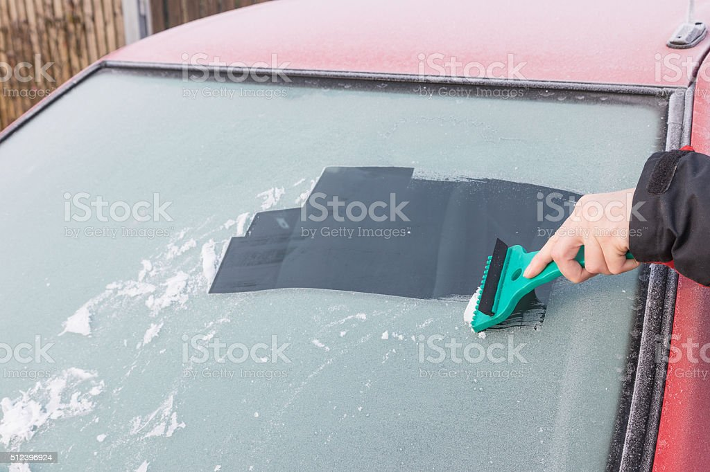 Hand is scraping ice from the windshield of the car stock photo
