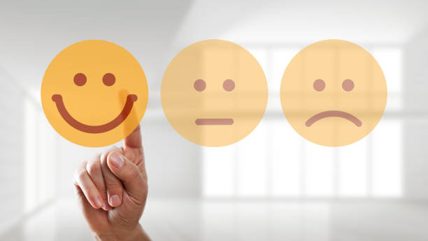 hand is selecting a happy mood smiley hand is selecting a happy mood smiley in front of empty room mental wellbeing stock pictures, royalty-free photos & images