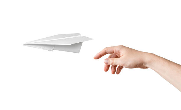hand is throwing origami paper airplane. isolated on white background. - samolot z papieru zdjęcia i obrazy z banku zdjęć