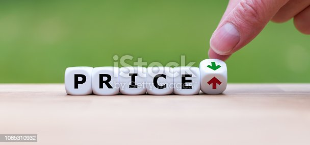 istock Hand is turning a dice and changes the direction of an arrow symbolizing that the price is going down (or vice versa) 1085310932