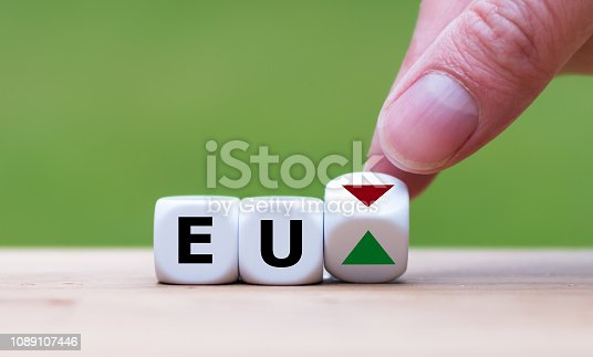Hand is turning a dice and changes the direction of an arrow symbolizing that European economy is changing the trend and goes up instead of down (or vice versa)